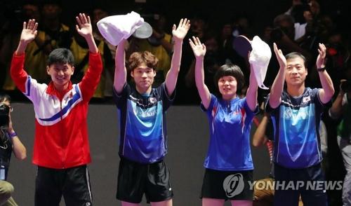 7月21日,2018年国际乒联世界巡回赛韩国公开赛混双决赛在大田进行,韩国选手张宇镇(左二)、朝鲜选手车孝芯(左三)组合获得冠军。图为赛后选手和韩朝主教练(右一和左一)向镜头挥手示意。(韩联社)