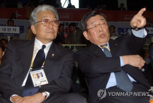 资料图片:2002年10月10日,在韩国釜山举行的第14届亚运会上,朝鲜体育相张雄(左)和金云龙观看跆拳道比赛。(韩联社)