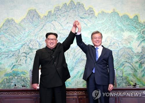 资料图片:4月27日,在板门店,韩朝首脑在联合宣言文本上签字后牵手高举。(韩联社)
