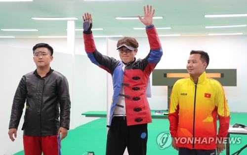 当地时间8月24日,在雅加达亚运会射击男子10米移动靶决赛中,韩国运动员郑有真(中)夺取金牌后庆祝胜利。左为银牌得主朝鲜选手。(韩联社)
