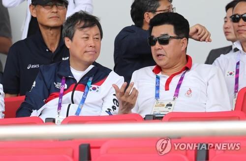 资料图片:当地时间8月22日,在印尼雅加达,韩国文化体育观光部长官都钟焕(左)与朝鲜体育相金一国一同观看2018雅加达亚运会赛艇项目韩朝联队的比赛。(韩联社)
