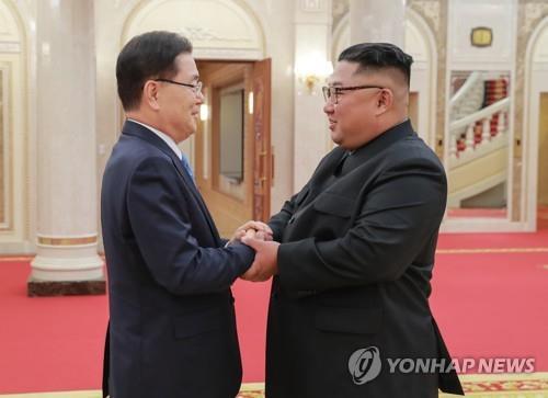 9月5日,在朝鲜平壤,访朝的韩国总统特使团团长、青瓦台国家安保室室长郑义溶(左)同朝鲜国务委员会委员长金正恩握手合影。(韩联社/青瓦台供图)