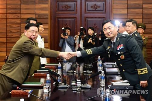 资料图片:6月14日,在韩朝边境板门店朝方一侧的统一阁举行的韩朝军事会谈上,韩朝军事会谈韩方代表团团长、国防部对朝政策官金度均(右)同朝方代表团团长、陆军中将安益山握手。这是韩朝将军级军事会谈自2007年12月后时隔10年6个月再次举行。(韩联社/联合采访团)
