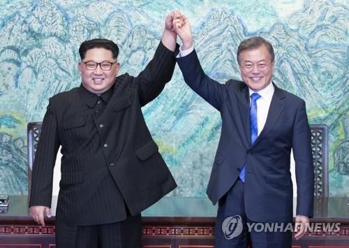 资料图片:4月27日,在韩朝边境板门店,韩国总统文在寅(右)与朝鲜国务委员会委员长金正恩交换《板门店宣言》后牵手举臂。(韩联社)