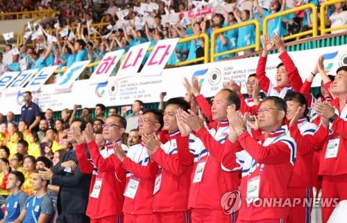 """资料图片:9月1日下午,在2018射击世锦赛开幕式上,朝鲜选手掌声欢迎朝鲜国旗""""人共旗""""入场。(韩联社)"""