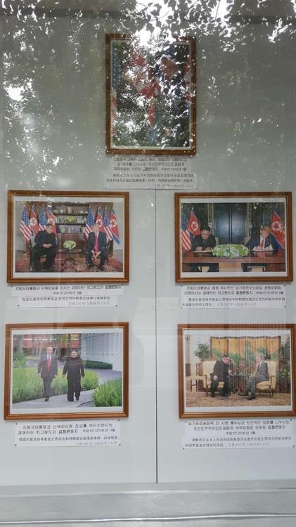 资料图片:7月29日,在韩朝停战协定签署65周年之际,朝鲜驻华大使馆外墙公告栏醒目位置张贴出韩国总统文在寅和美国总统特朗普的照片。(韩联社)