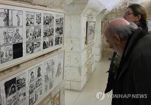 Visitors look at some of the works depicting Korean victims of Japan's wartime sexual slavery being exhibited at an international comic strip and cartoon festival in Angouleme, France, on Jan. 31, 2014. (Yonhap)