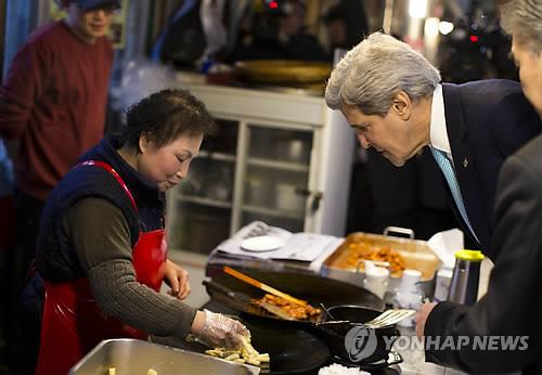 U.S. Secretary of State John Kerry waits for food during a tour of the Tong-in Market in Seoul on Feb. 13.