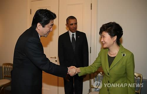 South Korean President Park Geun-hye and Japanese Prime Minister shake hands as U.S. President Barack Obama looks on during a meeting in The Hague on March 25. (Yonhap)