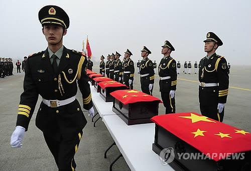 Chinese soldiers carry flag-draped coffins containing remains of Chinese war dead who were killed in the 1950-53 Korean War during a repatriation ceremony held at the Incheon International Airport on Marh 28, 2014. (Yonhap)