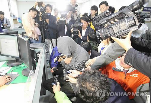 The captain (center) of the sunken ferry answers questions by the Coast Guard on April 17, 2014, a day after the passenger vessel carrying nearly 500 people sank in waters off South Korea's southern coast. (Yonhap)
