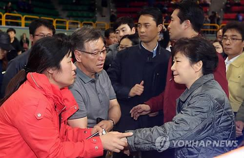 President Park Geun-hye shakes hands with one of families of those missing in the sinking of a ferry off South Korea's south coast during a visit to an indoor gymnasium near the accident site on April 17, 2014. (Yonhap)