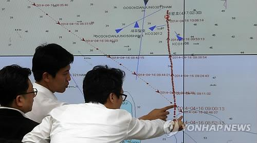Officials study the map from the Automatic Identification System (AIS) of the sunken ferry Sewol on April 17, 2014, showing the route of the ship before it capsized, leaving at least 10 dead and nearly 300 missing. (Yonhap)