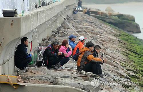 Families of missing passengers in the sinking of the ferry Sewol look at the waters close to the sinking site from a port on Jindo Island in southwestern South Korea on April 19, 2014. (Yonhap)