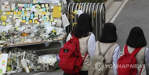 Pieces of paper and flowers are laid at the entrance of Danwon High School, which resumed classes after a one-week break on April 24, 2014, following the deadly sinking of a ferry carrying hundreds of its students off South Korea's southwest coast. (Yonhap)