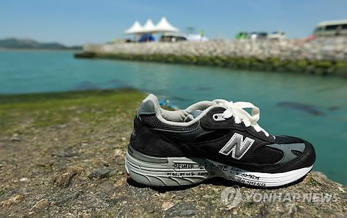 """A father puts a shoe in a nearby port in South Korea's southern island of Jindo on May 6, 2014, for his child who remains missing in the sinking of the ferry Sewol, leaving a message that read, """"Dear my last baby, your friend bought pretty new shoes. Mom, sister, and brother all miss you. We are waiting for you."""" (Yonhap)"""