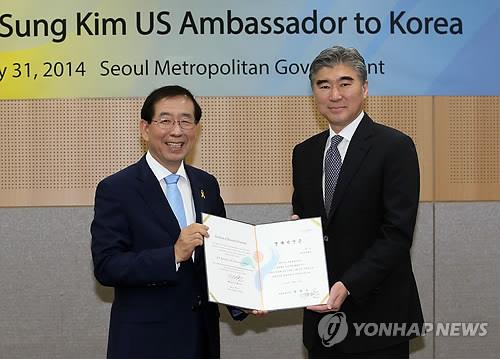 Sung Kim (R), the outgoing U.S. ambassador to South Korea, holds up a certificate of honorary Seoul citizenship with Mayor Park Won-soon at a ceremony on July 31, 2014. (Yonhap)