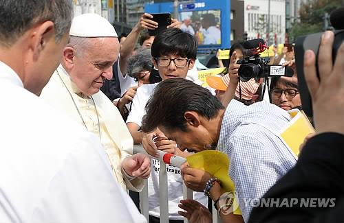 Pope Francis consoles one of the victims of South Korea's April ferry disaster before a Mass on Aug. 16, 2014, that beatified 124 Korean martyrs in Seoul. (Photo courtesy of the Committee for the Papal Visit to Korea)