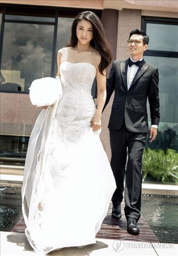This photo released by Seoul's Bom Film Productions Co. on Aug. 19, 2014, shows Chinese actress Tang Wei and South Korean filmmaker Kim Tae-yong formally tying the knot in a wedding ceremony attended only by their immediate families. (Photo courtesy of Bom Film Productions Co.) (Yonhap)