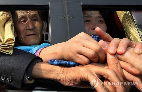 North Koreans on a bus and their South Korean family members bid painful farewells after their reunions at Mount Kumgang on North Korea's east coast on Feb. 25, 2014. (Yonhap file photo)