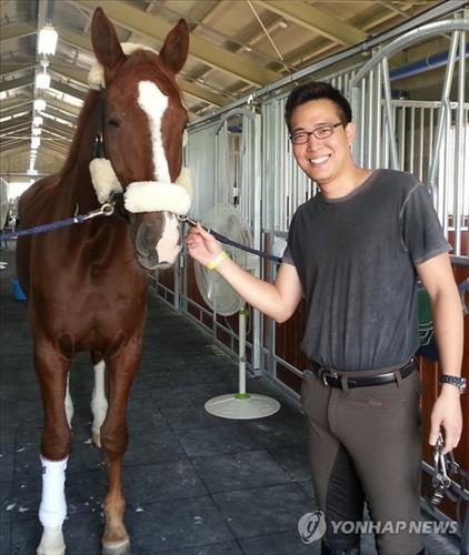 Kim Dong-seon, a South Korean rider set to compete in equestrian at this year's Incheon Asian Games, poses with his horse in Incheon on Sept. 16, 2014. (Yonhap)