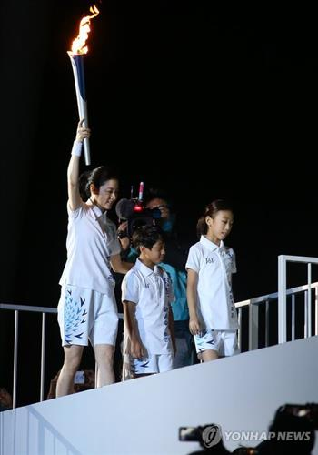 South Korean actress Lee Young-ae, far left, carries the Asian Games torch toward the cauldron during the event's opening ceremony on Sept. 19, 2014. (Yonhap)