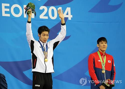 Kosuke Hagino of Japan raises his arms in celebration of his gold medal in the men's 200-meter freestyle race as Park Tae-hwan of South Korea stands next to him on the podium at the Incheon Asian Games on Sept. 21, 2014. (Yonhap)