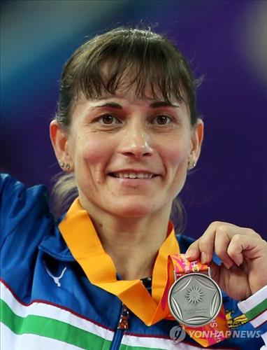 Uzbekistan's Oksana Chusovitina, 39, holds up her silver medal following the women's vault final at the Asian Games in Incheon. (Yonhap file photo)