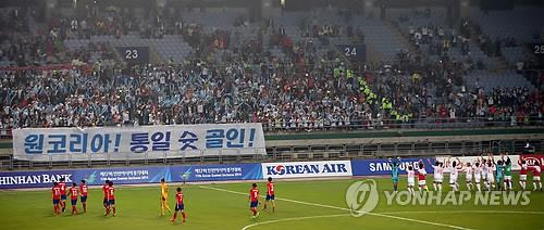 "South Koreans wave the banner that reads, ""One Korea, shoot goal-in for unification"" during the inter-Korean women's football match in South Korea's western port city of Incheon on Sept. 29, 2014. (Yonhap)"