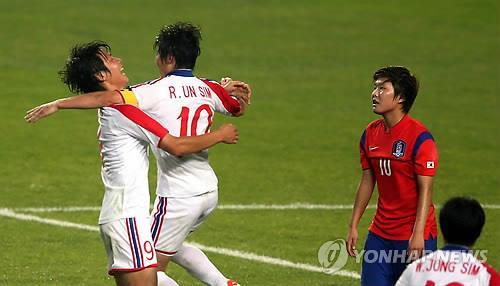 North Korean footballers Ho Un-byol, far left, and Ra Un-sim celebrate Ho's goal as South Korea's Ji So-yun looks on at Munhak Stadium in Incheon on Sept. 29, 2014. (Yonhap)