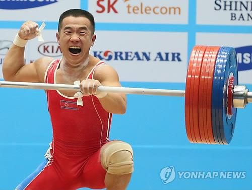 North Korean weightlifter Om Yun-chul pumps his fist after setting a world record in the men's 56-kilogram clean and jerk during the Asian Games on Sept. 20, 2014. (Yonhap file photo)