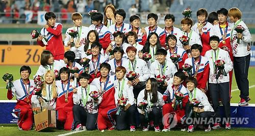 Football players from South Korea and North Korea get together for photos after the medal ceremony on Oct. 1, 2014, during the Incheon Asian Games. (Yonhap)