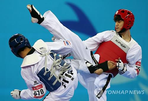 South Korea's Lee Dae-hoon, right, attacks Akkarin Kitwijarn of Thailand during their Asian Games taekwondo gold medal bout on Oct. 2, 2014. (Yonhap)