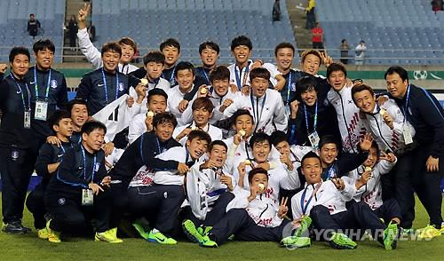 South Korean football players and coaches pose for photos after capturing the Asian Games gold medal on Oct. 2, 2014. (Yonhap)