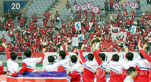 North Korean footballers greet South Koreans who cheered for them during the final competition on Oct. 1, 2014. (Yonhap file photo)