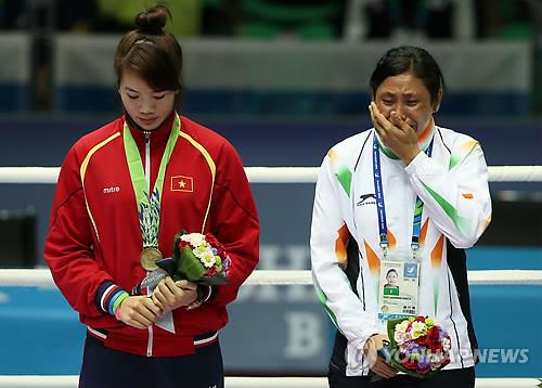 Indian boxer Sarita Devi (R) bursts into tears on Oct. 1, 2014 after winning the bronze medal in the women's lightweight division. She refused to accept the medal, saying it belongs to the silver medalist, Park Jin-a of South Korea. (Yonhap file photo)