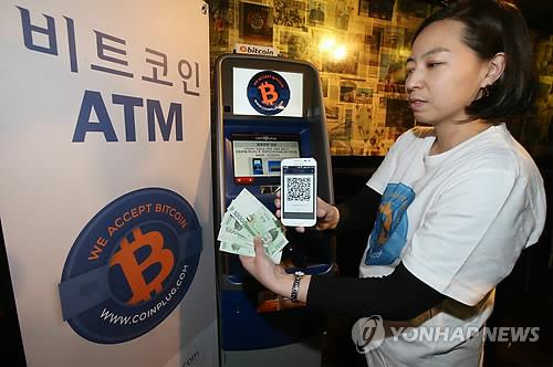 A woman shows Korean money withdrawn from an ATM that handles Bitcoin transactions, located at COEX Mall in southern Seoul. (Yonhap file photo)