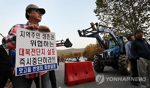 A resident in Paju, north of Seoul holds up a picket sign opposing conservative activists' attempts to fly leaflets to North Korea on Oct. 25, 2014. (Yonhap)