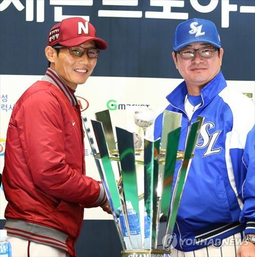 Yeom Kyung-yup (L), manager of the Nexen Heroes, and Ryu Joong-il, manager of the Samsung Lions, shake hands next to the Korean Series championship trophy in Daegu on Nov. 3, 2014. (Yonhap)