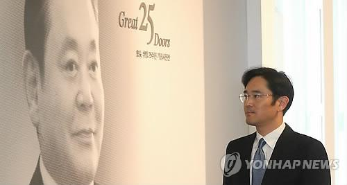 This file photo, taken on Nov. 30, 2012, shows Lee Jay-yong, the de facto heir of Samsung Group, walking by Lee Kun-hee's picture at the ceremony to commemorate the 25th anniversary of his father's inauguration. (Yonhap file photo)