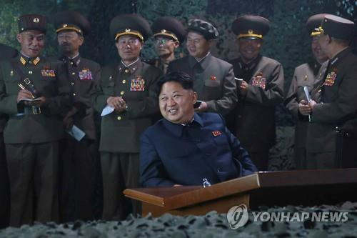 North Korean leader Kim Jong-un (C) watches a nighttime firing drill by navy warships and ground artillery sub-units in this photo carried by the North Korean communist party's official newspaper, the Rodong Sinmun, on June 16, 2015. (Yonhap)