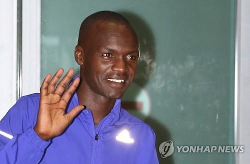 Wilson Loyanae Erupe, a marathoner born in Kenya who hopes to become a South Korean citizen, waves at cameras after arriving at Incheon International Airport on June 23, 2015. (Yonhap)