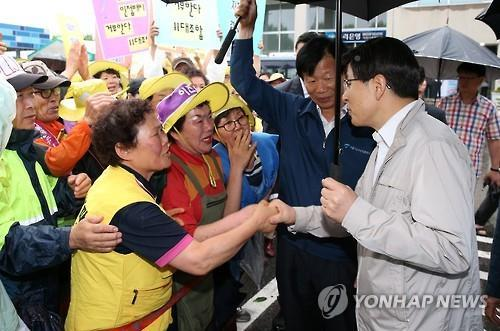 South Korean Prime Minister Hwang Kyo-ahn speaks with shop owners and visitors at a fish market in Seoul on June 26, 2015, as the government has struggled to keep the local economy afloat amid the outbreak of Middle East Respiratory Syndrome. (Yonhap)