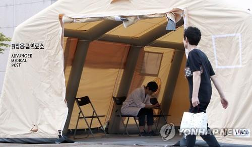 In this file photo, taken on June 21, 2015, a medical worker is seen inside a makeshift medical post set up to check people with symptoms of MERS while apparently wearing no protect gears. The World Health Organization has pointed to the lack of information about the infectious disease among medical workers and the general public in South Korea as a major factor driving the outbreak in the country. (Yonhap)