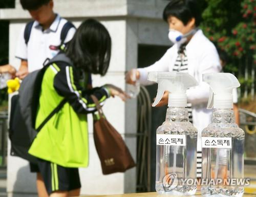A teacher sprays disinfectant into the hands of a female student at a junior high school in Seoul, South Korea in this file photo, taken on June 20, 2015. (Yonhap)