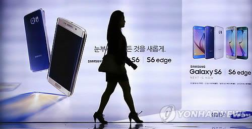 This undated file photo shows a person walking in front of a smartphone advertisement in Seoul. Asia's fourth-largest economy saw its smartphone penetration rate reach 83 percent as of end-March, according to the data compiled by Digieco, a research center run by South Korea's mobile carrier KT Corp., on July 8, 2015. (Yonhap)
