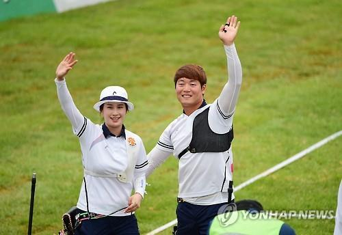 South Korean archers Ki Bo-bae (L) and Lee Seung-yun wave to the crowd after winning the gold medal in mixed team recurve archery at Gwangju International Archery Center on July 8, 2015. (Yonhap)
