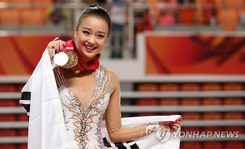 South Korean rhythmic gymnast Son Yeon-jae holds up her medals at the Universiade in Gwangju on July 13, 2015. (Yonhap)