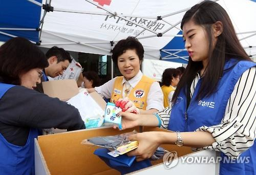 In this file photo taken on July 21, 2015, employees from affiliates of Samsung Group fill a box with relief supplies during a charity event at a Red Cross office in Seoul. (Yonhap)
