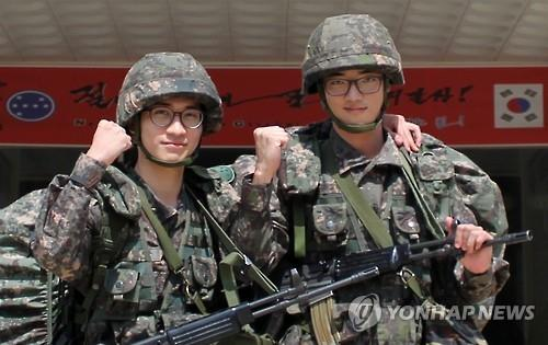This undated photo, releashed on Aug. 24, 2015, by the Army headquarters, shows two South Korean soldiers, Sgt. Chun Moon-kyun (L) and Sgt. Joo Chan-joon, posing for a photo. The two, from the 7th Division, have decided to have their discharge from the Army postponed at a time when tensions between the Koreas have risen dramatically after South Korea accused North Korea of orchestrating a land mine attack that maimed two South Korean soldiers. The North also fired artillery shells across the border on Aug. 20, prompting South Korea to fire back dozens of shells. (Yonhap)